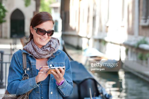 Female tourist in Italy with smartphone next to a canal