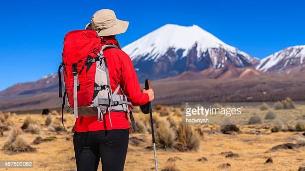 Female tourist looking at Parinacota volcano on the bolivian altiplano