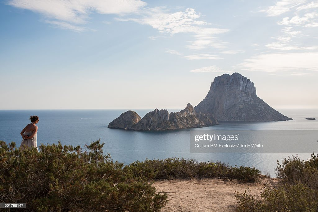 Female tourist looking out to rocky island, Ibiza, Spain : Stock Photo