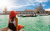 Attractive, female tourist enjoys the view to the Basilica di Santa Maria della Salute and Canale Grande in Venice, Italy