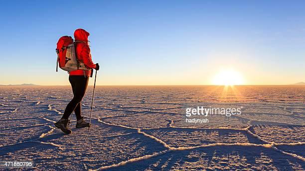 Female tourist on Salar de Uyuni during sunset, Altiplano Bolivia
