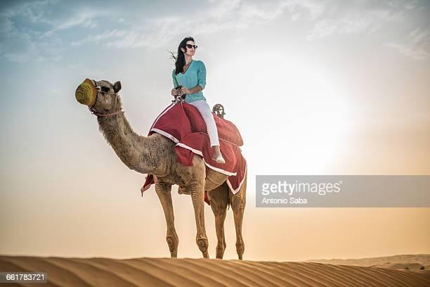 Female tourist riding camel in desert, Dubai, United Arab Emirates