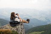 Hiker girl with backpack taking self portrait in beautiful scenery on a rock in ukrainian carpathians