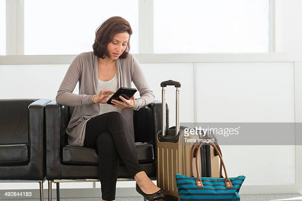 Female tourist using tablet pc at airport, Jersey City, New Jersey, USA