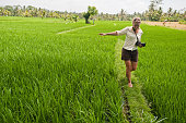 Female tourist walking along grass wall between two rice paddies near Ubud, Bali, Indonesia