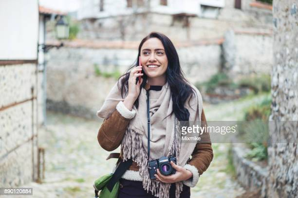 Female tourist walking and talking on the phone