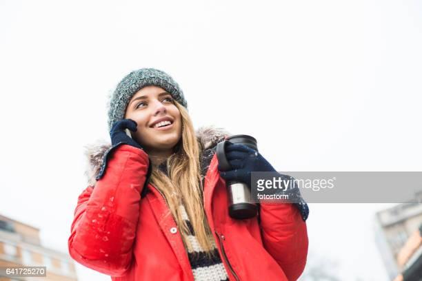 携帯電話で話しの旅行マグカップの女性観光客