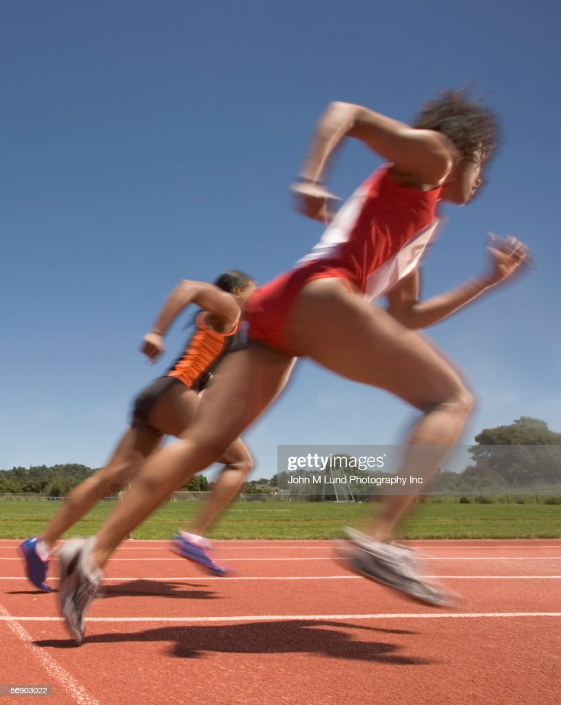Female track participants at speed : Stock Photo