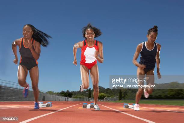 Female track runners race from starting line