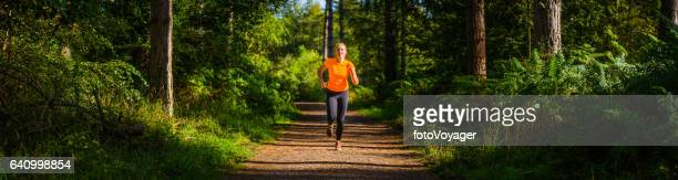 Female trail runner running along forest track through idyllic woodland