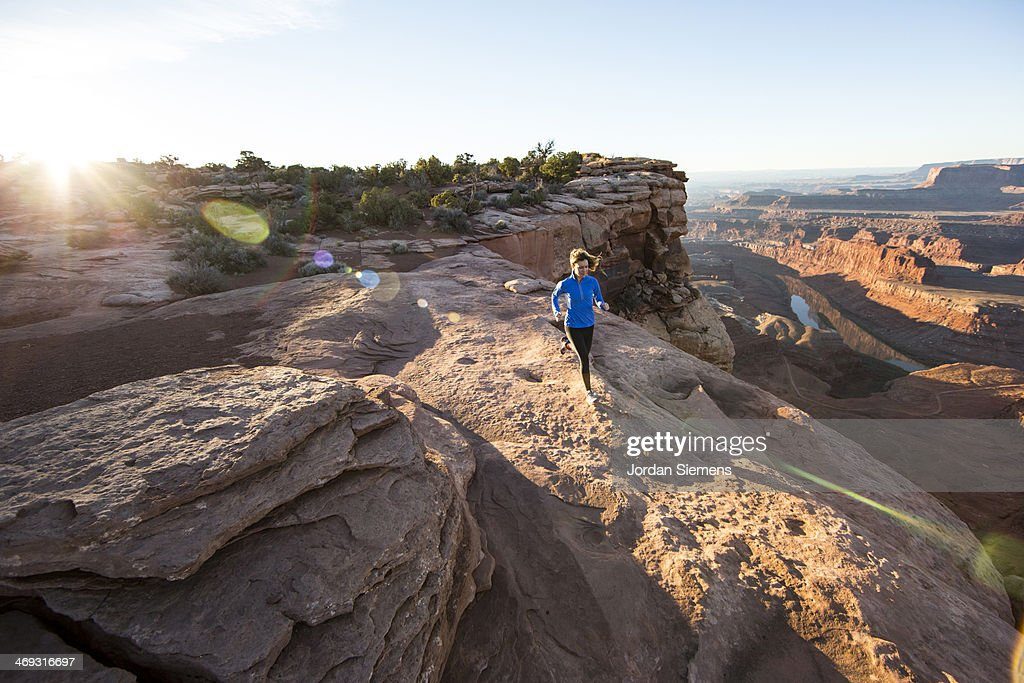 Female trail running on red rocks