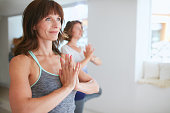 Portrait of fitness woman in doing yoga. Female trainer with student practicing Vrikshasana. Tree Pose with hands in Namaste gesture at gym.