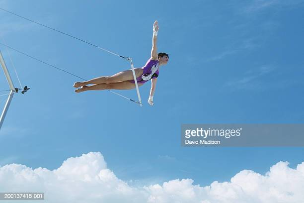 Female trapeze artist mid-air, balancing on hips