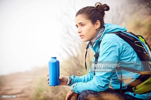 Female traveler holding water bottle during foggy weather
