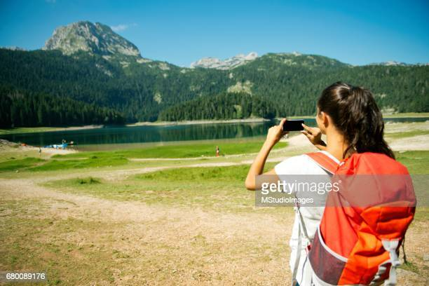 Female traveler making a photo of a beautiful place