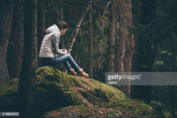 Female traveler uses a smartphone in a forest