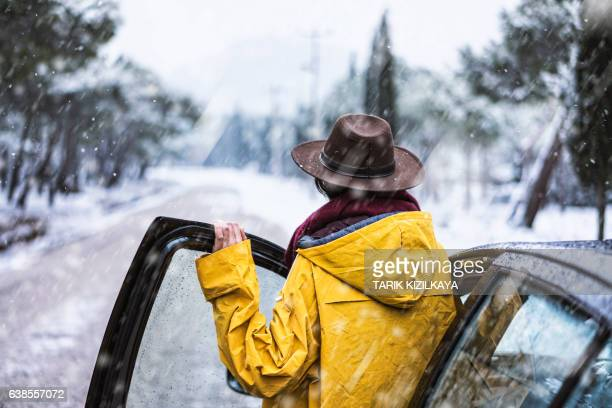Female traveler with yellow rain coat driving on snowy day