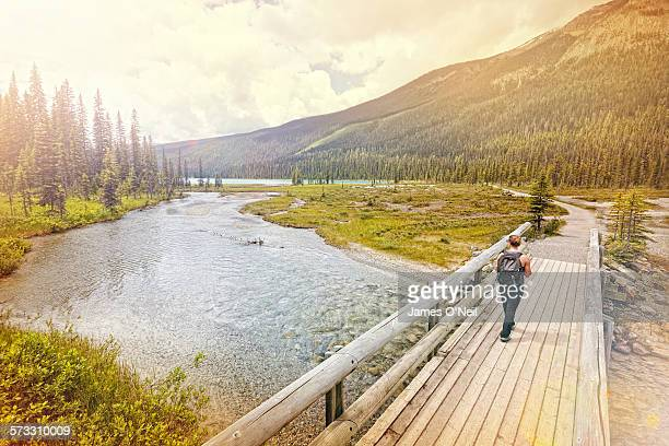 Female traveller hiking across bridge