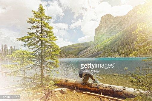 female traveller sitting viewing alpine lake