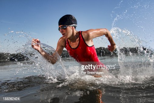 Female triathlete running out of water