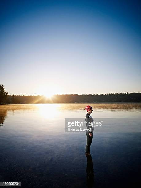 Female triathlete standing in water at sunrise