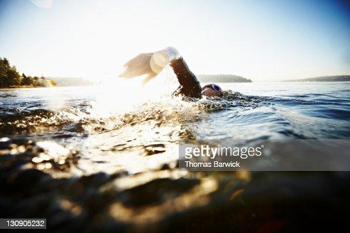 Female triathlete swimming freestyle at sunrise