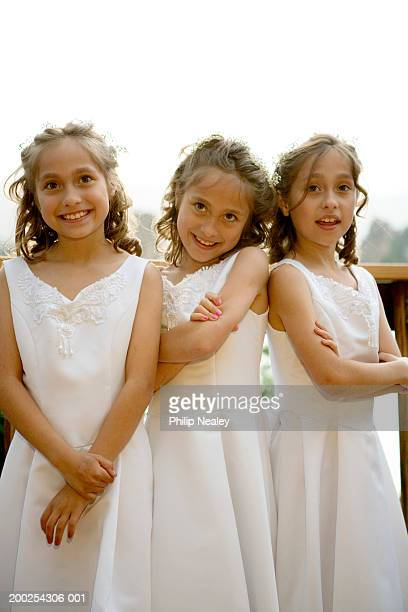 Female triplets (7-9) wearing formal dresses, portrait