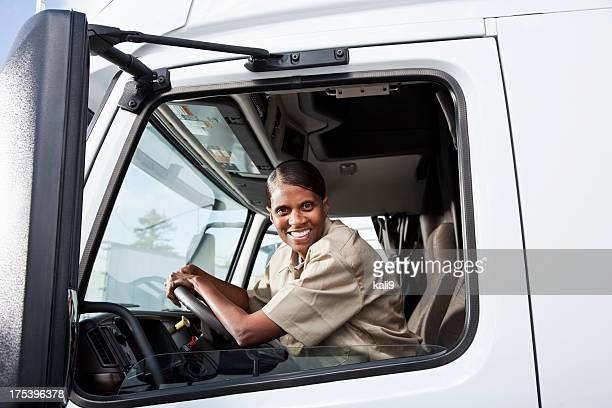 Female truck driver sitting in cab of semi-truck