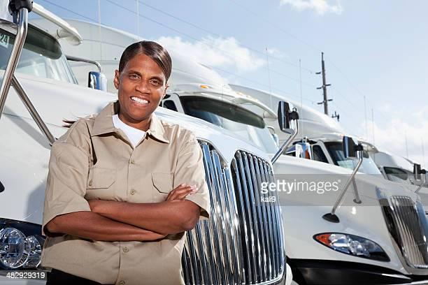 Female truck driver standing by semi-trucks