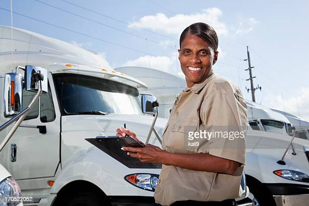 Female truck driver standing by semi-trucks with clipboard