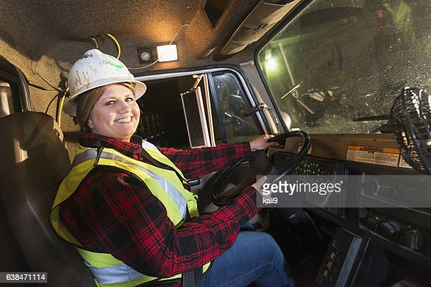 Female truck driver wearing safety vest and hard hat