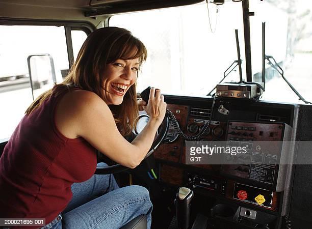 Female trucker holding CB radio receiver