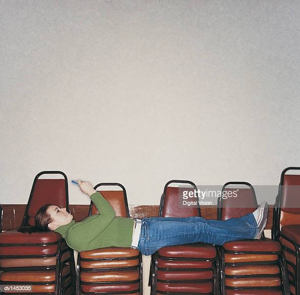 Female University Student Lying on a Stack of Chairs