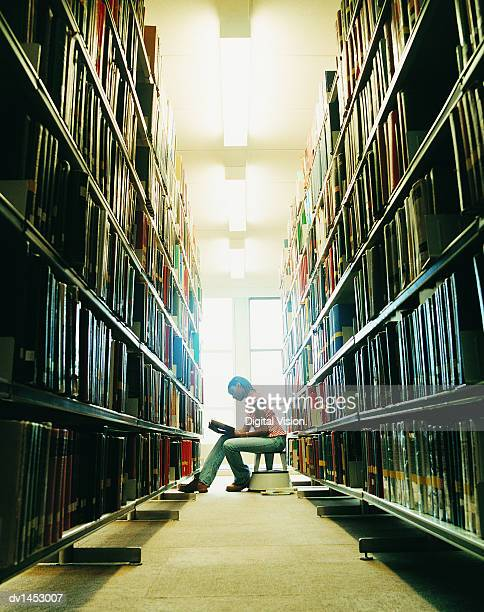 Female University Student Reading a Book in a Library