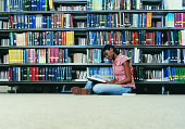Female University Student Sitting on a Library Floor Reading a Book