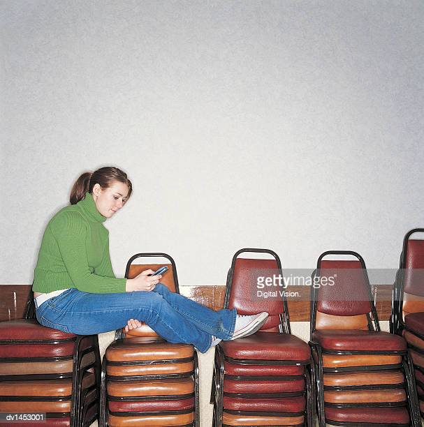 Female University Student Sitting on a Stack of Chairs Dialling Her Mobile Phone