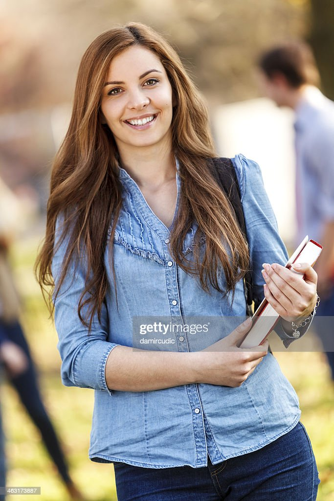 Female university student with book and tablet outdoors