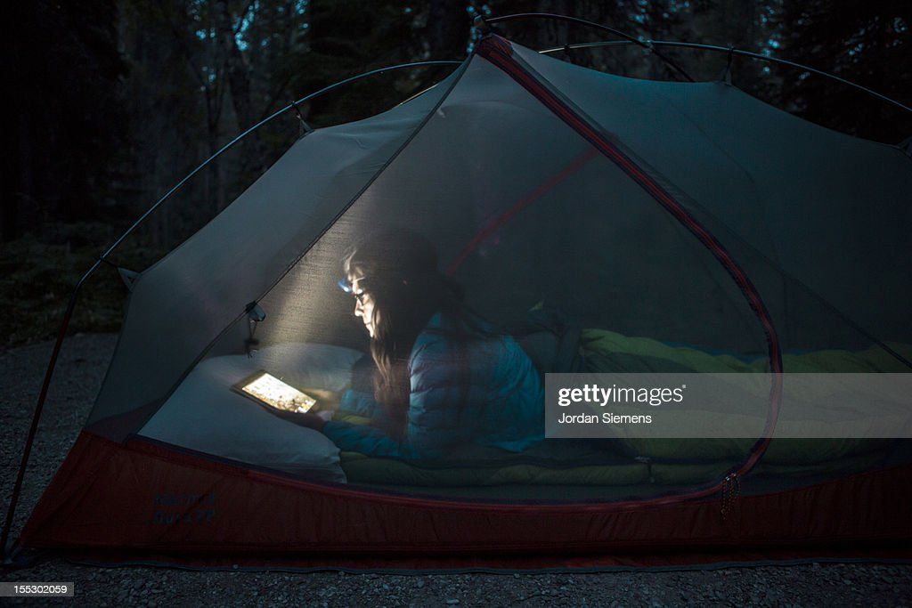 A female using an iPad in her tent. : Stock Photo