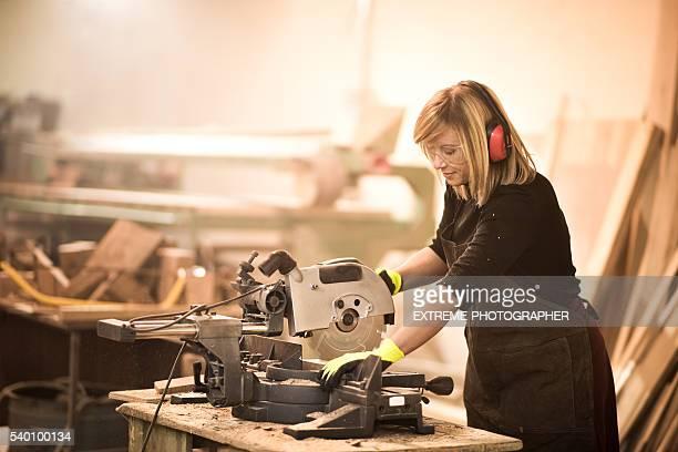 Female using circular saw in workshop