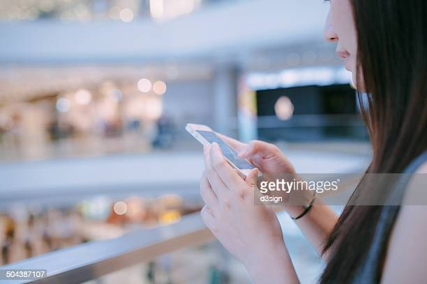 Female using smartphone in shopping mall