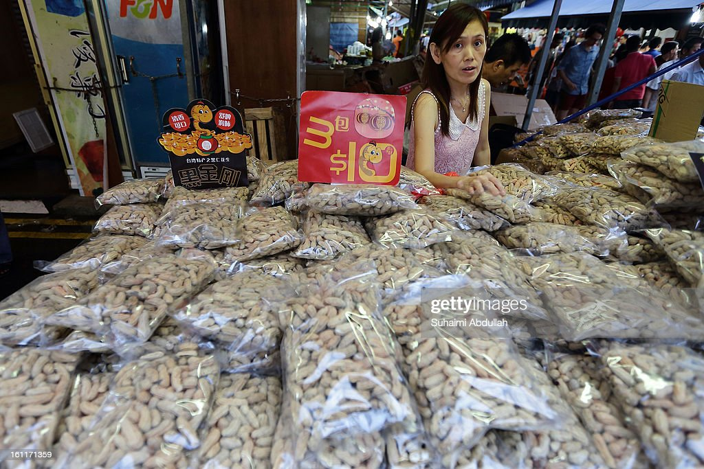 A female vendor is seen selling groundnuts in Chinatown on February 9, 2013 in Singapore. Thousands gathered today to celebrate the Chinese New Year and welcome the the Year of the Snake, with new year's day falling on February 10. Chinese new Year is the most important festival in the Chinese calendar and is celebrated in Singapore and many other Southeast Asian countries with significant Chinese Populations.