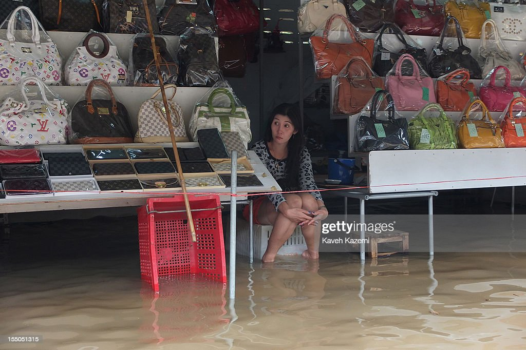 A female vendor with her feet in water sells Thai made handbags in her shop situated on the water in floating market on October 14 in Damnoen Saduak, Thailand. Damnoen Saduak is a district in the province of Ratchaburi in central Thailand. The central town has become a tourist attraction with its famous floating market.