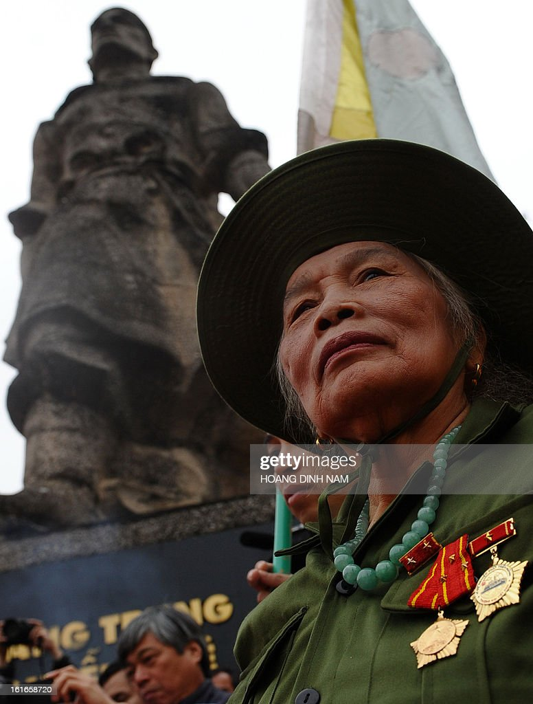A female veteran of the Vietnam War wearing former Vietcong dress stands in front of the statue of King Quang Trung during a ceremony to mark the 224th anniversary of Vietnam's Dong Da victory over Chinese invading troops in the spring of 1789 at the site of the historical battlefield in Hanoi on February 14, 2013. AFP PHOTO/HOANG DINH Nam