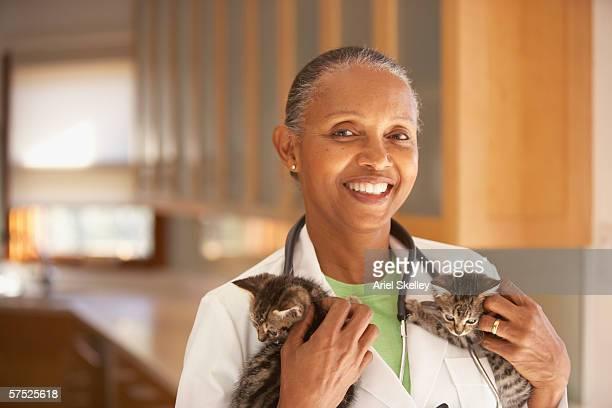 Female veterinarian holding kittens