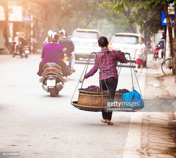 Female Vietnamese street merchant carrying her food by foot