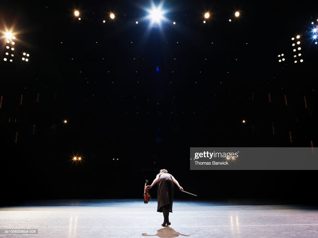 Female violinist bowing on stage, rear view