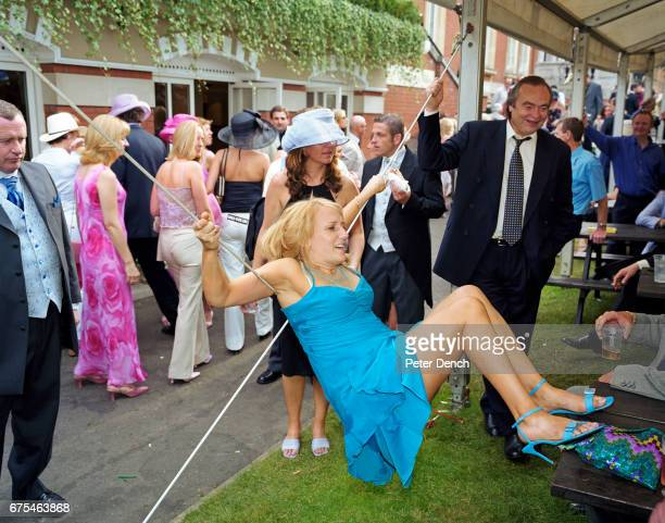 A female visitor to Royal Ascot hangs from the support of a hospitality tent June 2002