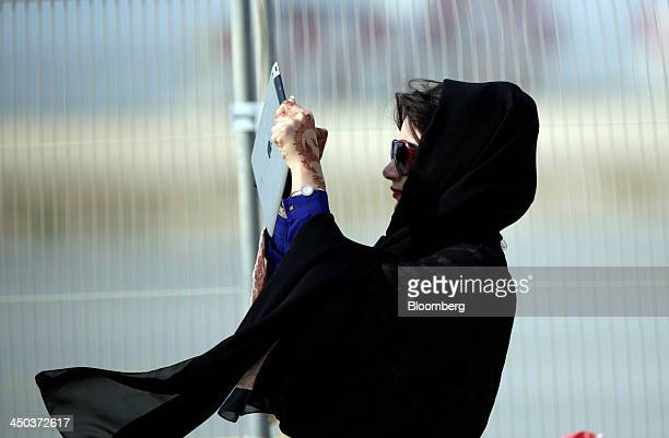 A female visitor uses her Apple Inc iPad tablet to photograph aircraft during the 13th Dubai Airshow at Dubai World Central in Dubai United Arab...