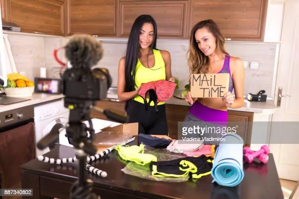 Female vloggers unpacking box with sportswear