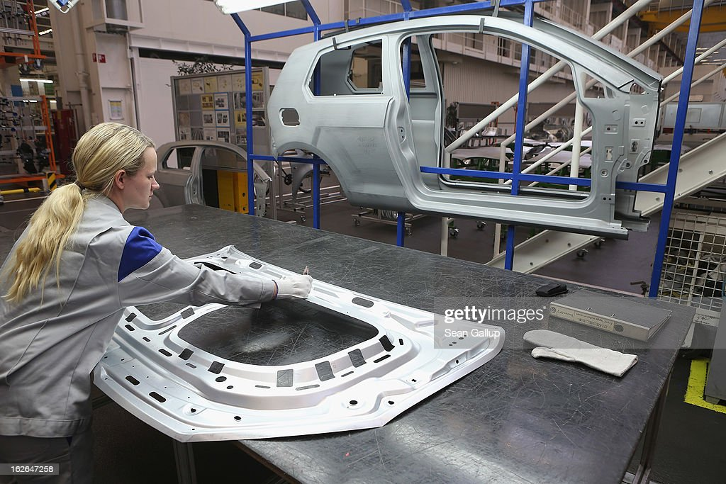 A female Volkswagen employee performs a quality check on a stamped car body part at the Volkswagen factory on February 25, 2013 in Wolfsburg, Germany. Volkswagen will announce financial results for 2012 on March 14.